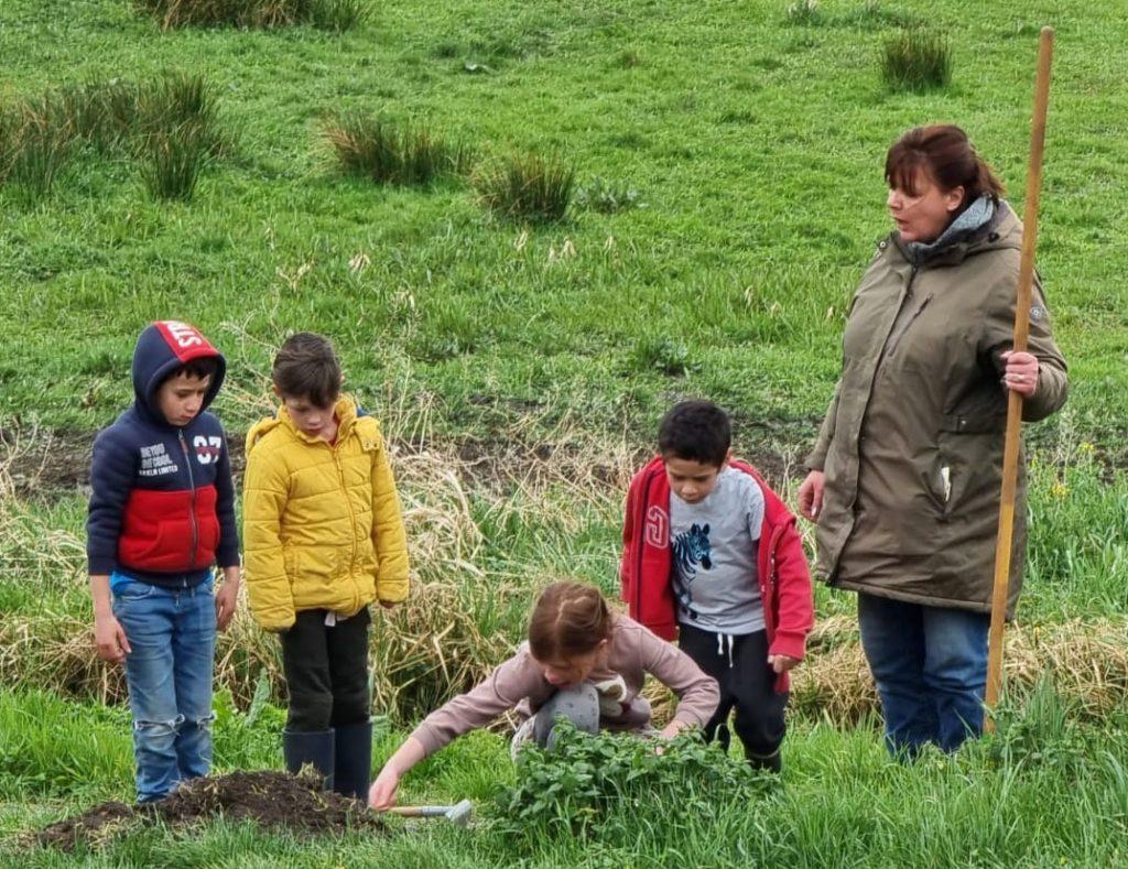 4 kinderen zijn de berm aan het inzaaien. 1 volwassene met een hark in de linkerhand kijkt toe